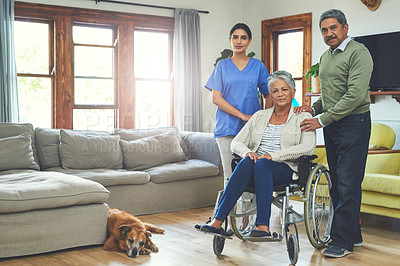 Buy stock photo Portrait of a cheerful woman seated in a wheelchair while being supported by her husband and a young female nurse inside at home