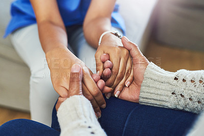 Buy stock photo Shot of an unrecognizable female nurse holding a patient's hands in support while being seated on a couch at home during the day