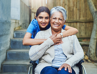 Buy stock photo Portrait of a cheerful young female nurse holding a elderly patient in a wheelchair as support outside during the day