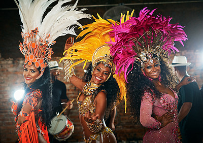 Buy stock photo Cropped portrait of three beautiful samba dancers performing in a carnival with their band