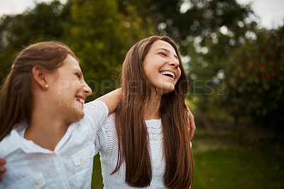 Buy stock photo Cropped shot of two young sisters enjoying their time together in the park