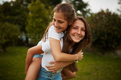Buy stock photo Cropped portrait of a young girl giving her younger sister a piggyback ride outdoors
