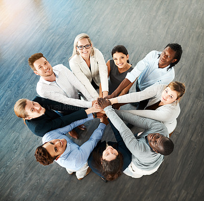 Buy stock photo High angle portrait of a group of young businesspeople joining hands in solidarity in a modern office