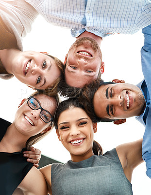 Buy stock photo Low angle portrait of a group of young businesspeople huddled together in solidarity