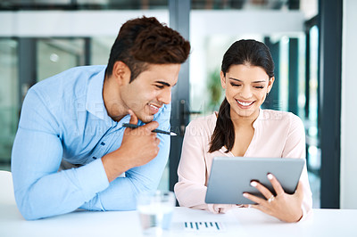 Buy stock photo Shot of a young businesswoman and businessman using a digital tablet together in a modern office