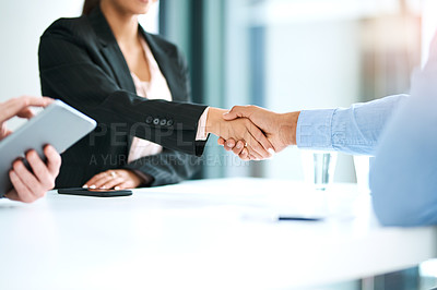 Buy stock photo Shot of a businesswoman shaking hands with a businessman during a meeting in a modern office