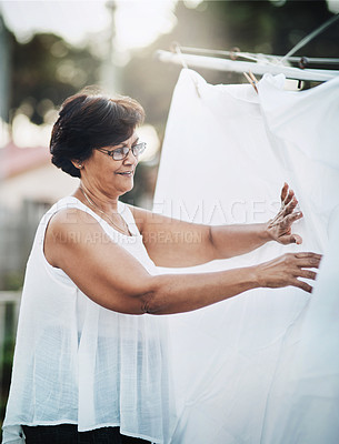 Buy stock photo Shot of a mature woman hanging up laundry on a washing line outdoors