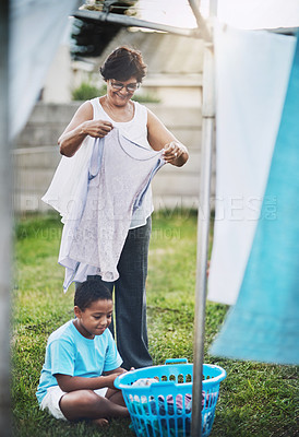 Buy stock photo Shot of a grandmother and her grandson hanging laundry together outdoors