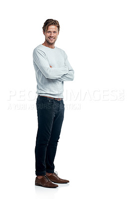 Buy stock photo Studio portrait of a handsome young man standing with his arms folded against a white background