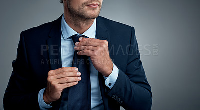 Buy stock photo Studio shot of an unrecognizable businessman adjusting his tie against a grey background