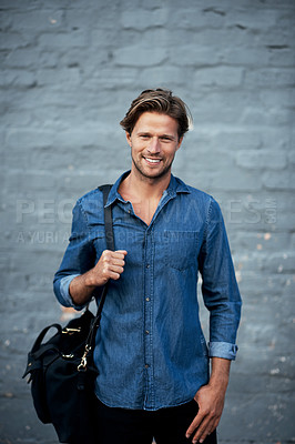 Buy stock photo Cropped portrait of a handsome young man standing with his bag against a grey brick wall