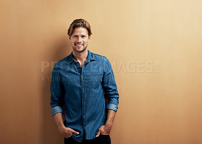 Buy stock photo Studio portrait of a handsome young man standing with his hands in his pockets against a bronze background