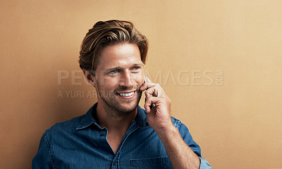 Buy stock photo Studio shot of a handsome young man using his cellphone while standing against a bronze background