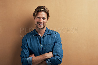 Buy stock photo Studio portrait of a handsome young man standing with his arms folded against a bronze background