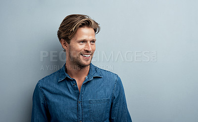 Buy stock photo Studio shot of a handsome young man standing against a grey background