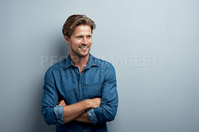 Buy stock photo Studio shot of a handsome young man standing with his arms folded against a grey background