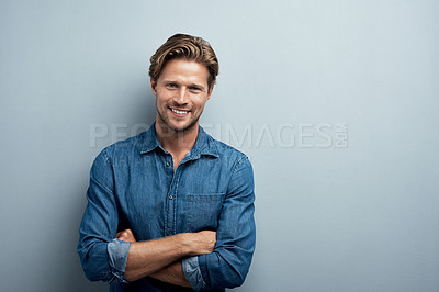 Buy stock photo Studio portrait of a handsome young man standing with his arms folded against a grey background