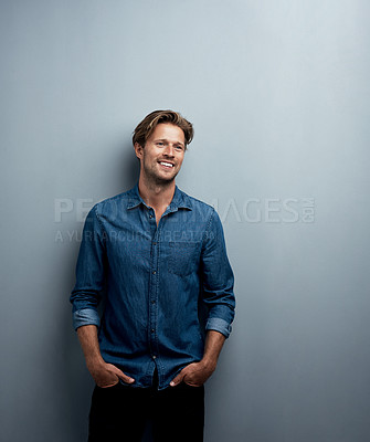 Buy stock photo Studio shot of a handsome young man standing with his hands in his pockets against a grey background