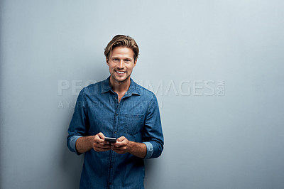 Buy stock photo Studio portrait of a handsome young man using his cellphone while standing against a grey background