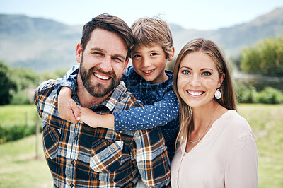 Buy stock photo Shot of a happy young family of three spending a day outdoors together