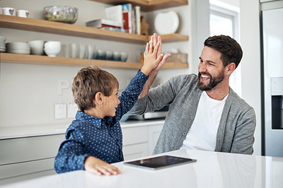 Buy stock photo Shot of a father and his little son high fiving each other at home