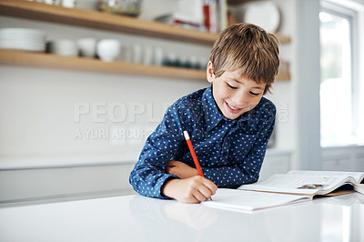 Buy stock photo Shot of a little boy doing his homework at home