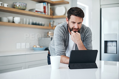 Buy stock photo Shot of a handsome young man using a digital tablet on the kitchen counter at home