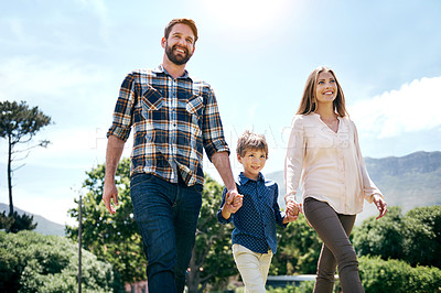 Buy stock photo Shot of a happy young family of three going for a walk together outdoors
