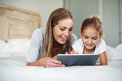 Buy stock photo Shot of an adorable little girl and her beautiful mother using a tablet at home