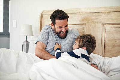 Buy stock photo Shot of a father tickling his little son in bed at home