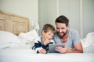 Buy stock photo Shot of a father and his little son using a digital tablet together in bed at home