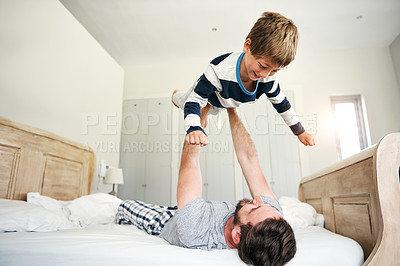Buy stock photo Shot of a father and his little son having fun in bed at home
