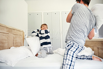 Buy stock photo Shot of a father and his little son having a pillow fight in the bedroom at home