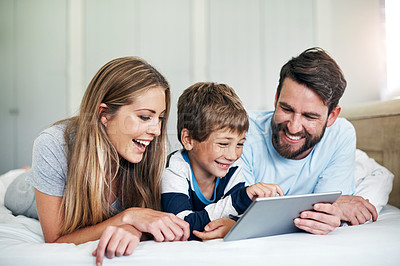 Buy stock photo Shot of a little boy using a digital tablet with his parents in bed at home