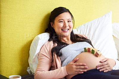 Buy stock photo Portrait of a pregnant woman lying down with wooden baby blocks on her belly at home
