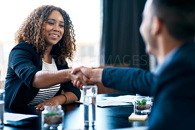 Buy stock photo Cropped shot of two business colleagues shaking hands during a meeting in the boardroom
