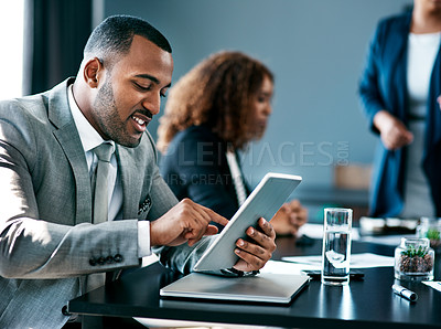 Buy stock photo Cropped shot of a handsome young businessman working on his tablet during a meeting in the boardroom