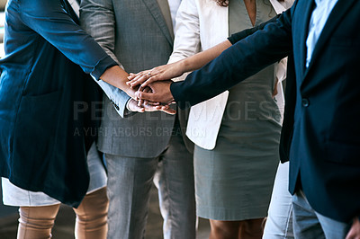Buy stock photo Cropped shot of a group of unrecognizable businesspeople standing with their hands in a huddle in the office