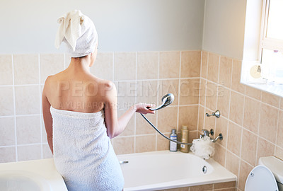 Buy stock photo Rearview shot of an unrecognizable woman getting ready to take a bath at home