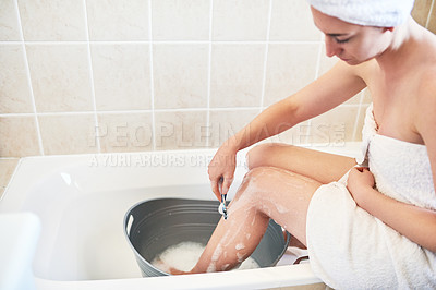 Buy stock photo Cropped shot of a young woman shaving her legs in a bucket of water in the bathroom at home