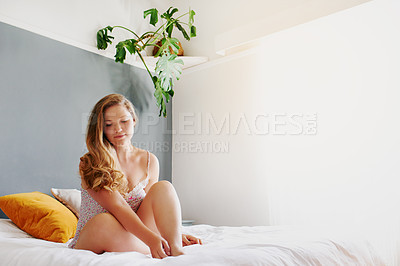 Buy stock photo Full length shot of an attractive young woman sitting on her bed while in her pyjamas