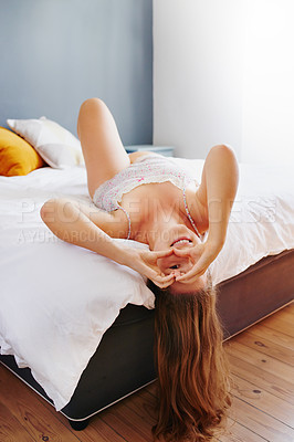 Buy stock photo High angle portrait of an attractive young woman looking through a heart shaped gap between her hands while lying on her bed