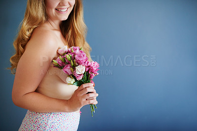 Buy stock photo Studio shot of an unrecognizable young woman holding a bouquet of flowers while standing in her underwear against a blue background