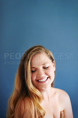 Buy stock photo Studio shot of a cheerful young woman wearing only her underwear while covering herself up and standing against a blue background