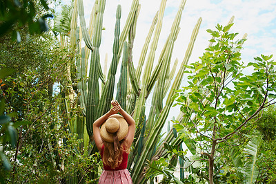 Buy stock photo Rearview shot of an unrecognizable woman in the backyard at home