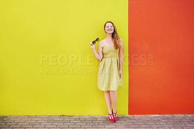 Buy stock photo Shot of a beautiful young woman posing against a bright yellow and orange wall outside