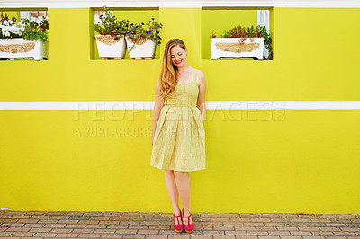 Buy stock photo Shot of a beautiful young woman posing against a bright yellow wall outside