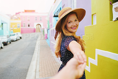 Buy stock photo POV shot of a beautiful young woman holding her boyfriends hand while walking amongst colourful homes outside