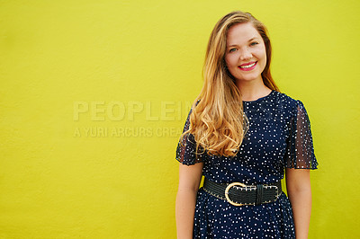 Buy stock photo Cropped shot of a beautiful young woman posing against a bright yellow wall outside