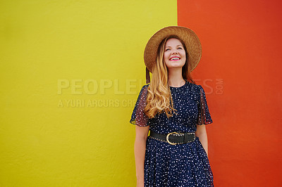 Buy stock photo Cropped shot of a beautiful young woman posing against a bright yellow and orange wall outside